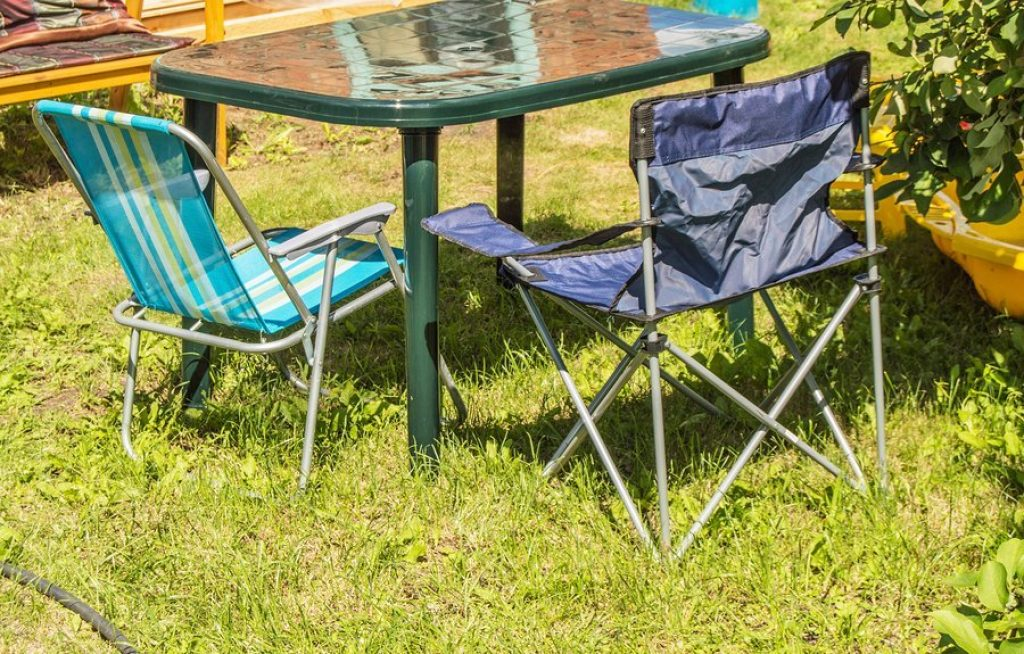 Plastic folding table and folding chairs for barbecuing on the grass on a sunny summer day