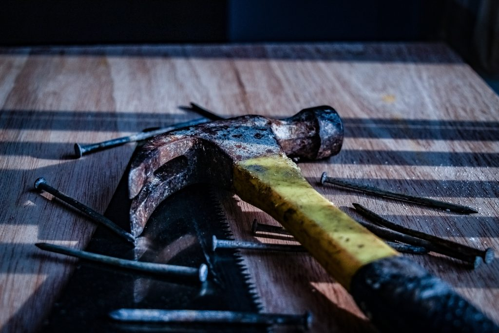 black and yellow claw hammer and nails on a table