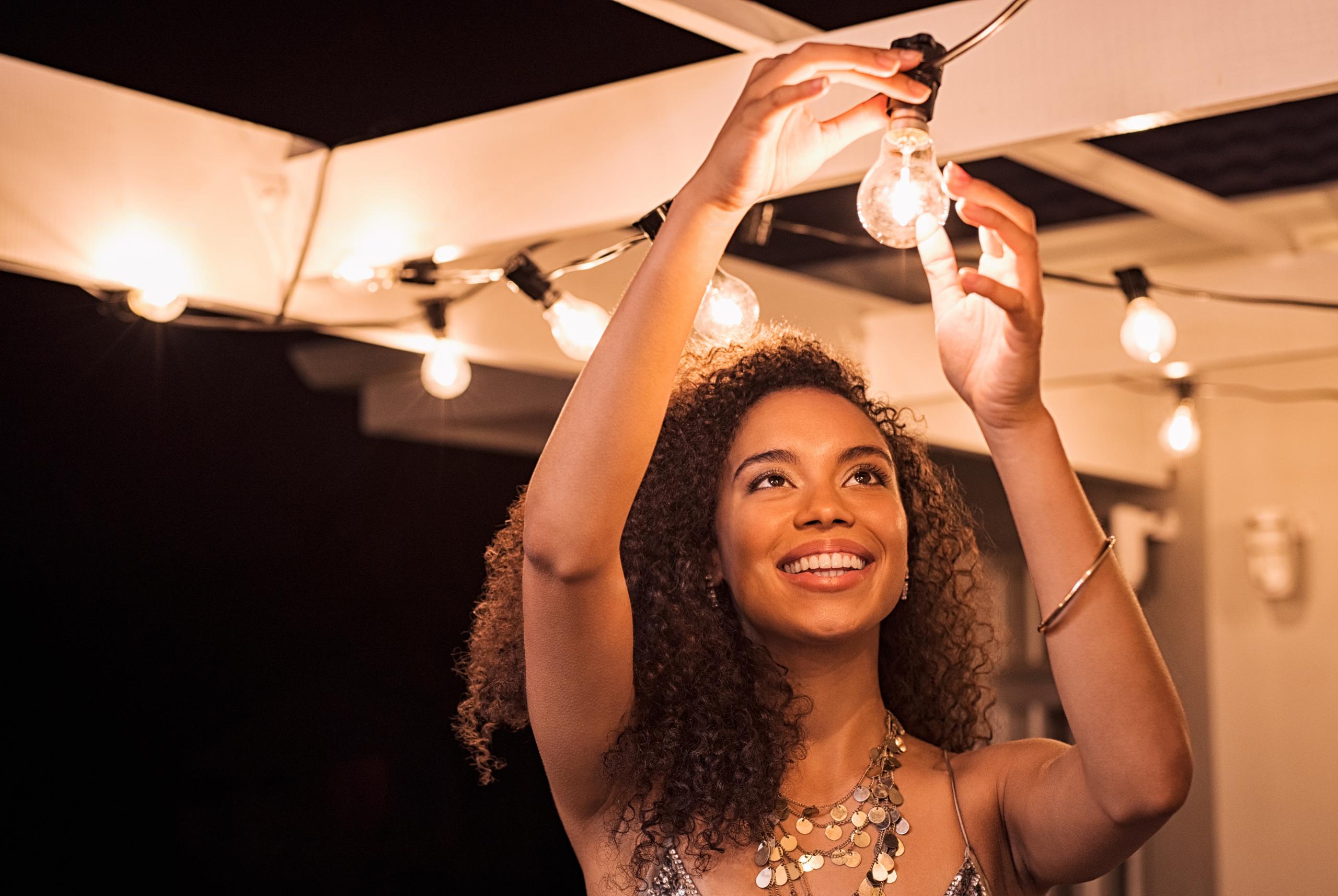 woman setting up party festoon lights